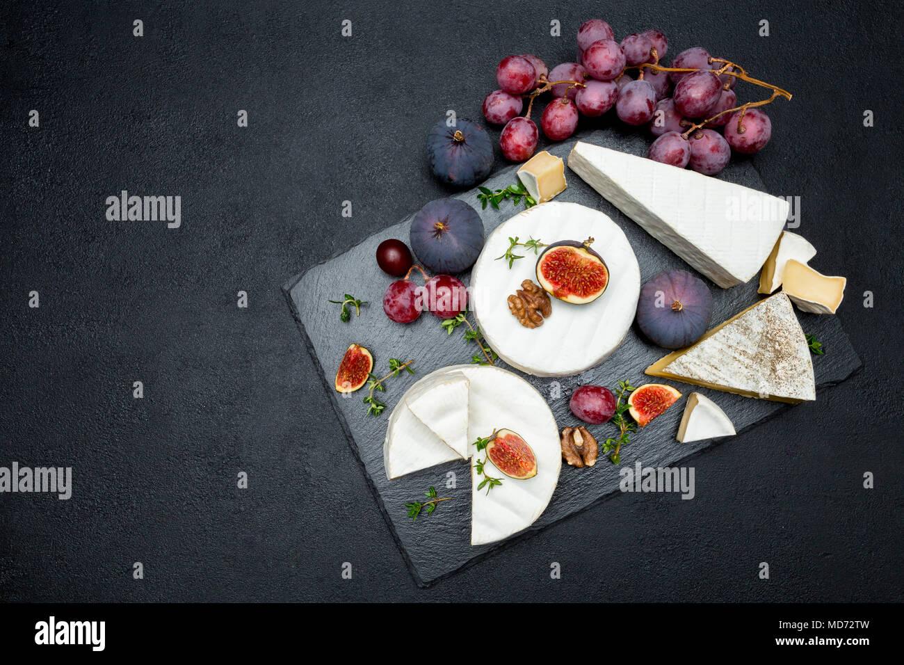 Formaggio Camembert e tagliare una fetta su pietra che serve board Immagini Stock