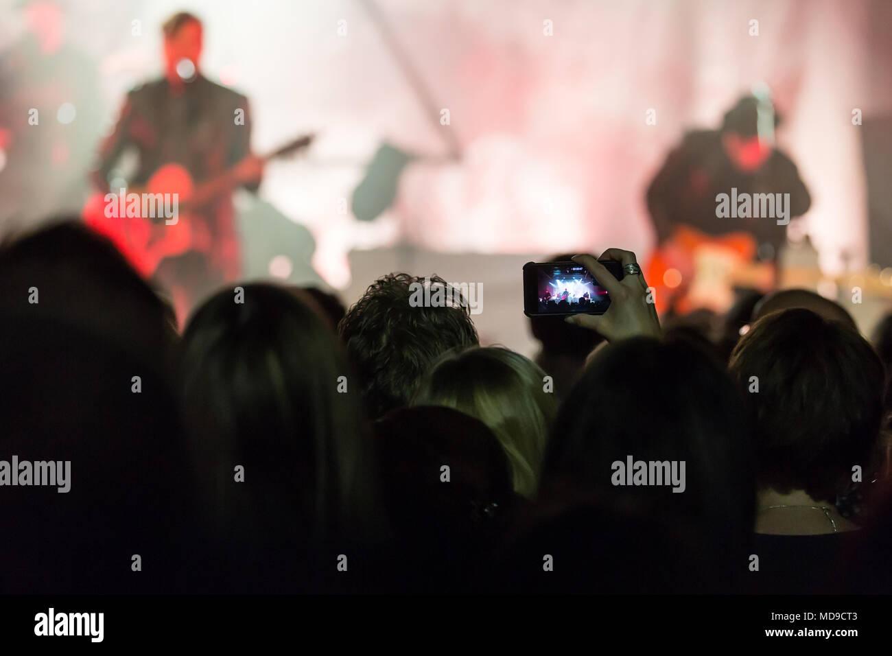 Concertgoer prende una foto con il mio telefono cellulare al concerto della banda musicale svizzera 77 Bombay Street live at Schüür Lucerna, Svizzera Immagini Stock