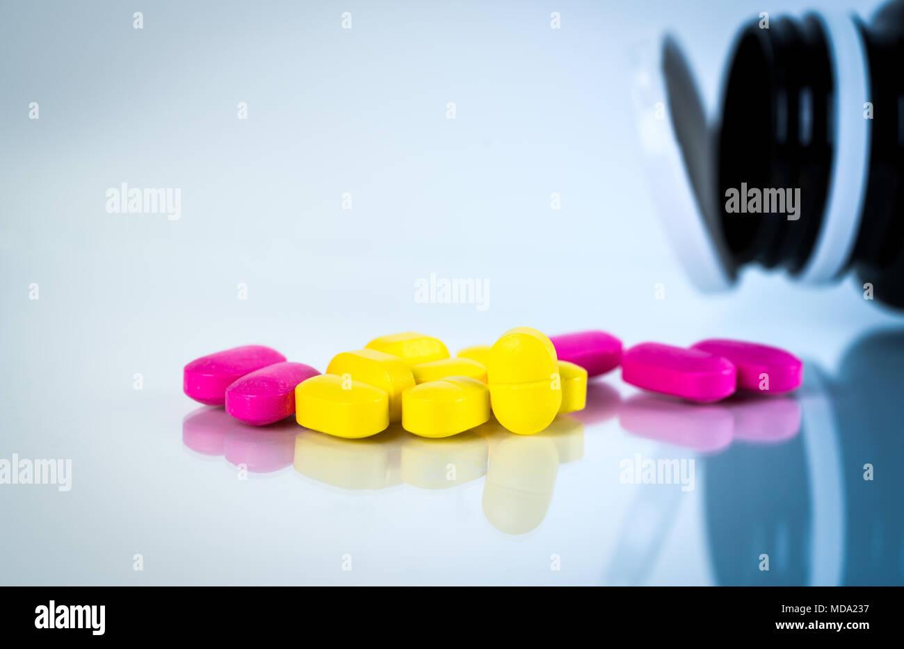 Giallo e rosa compressa ovale pillole con ombre su sfondo bianco con le pillole sfocata bottiglia. Da lieve a moderata la gestione del dolore. Killer del dolore medicina. Foto Stock