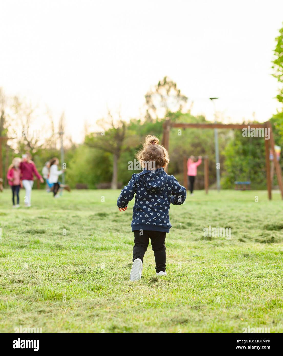 Bambina corre da dietro al parco a giocare con gli altri bambini. Immagini Stock