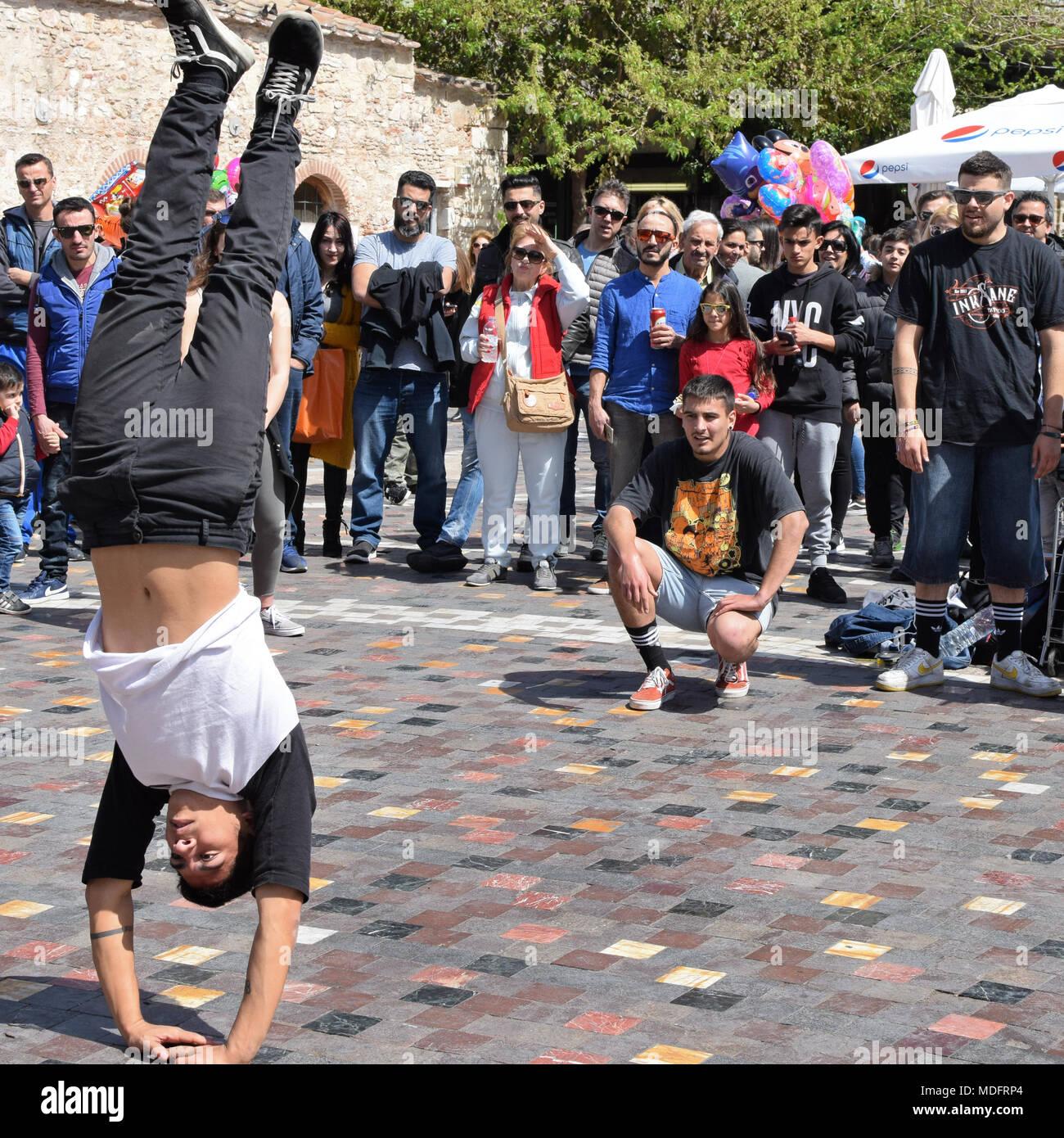 Atene, Grecia - Aprile 1, 2018: uomo di eseguire breakdance handstand spostare e la folla di gente a guardare. Street dancing cultura giovanile. Immagini Stock