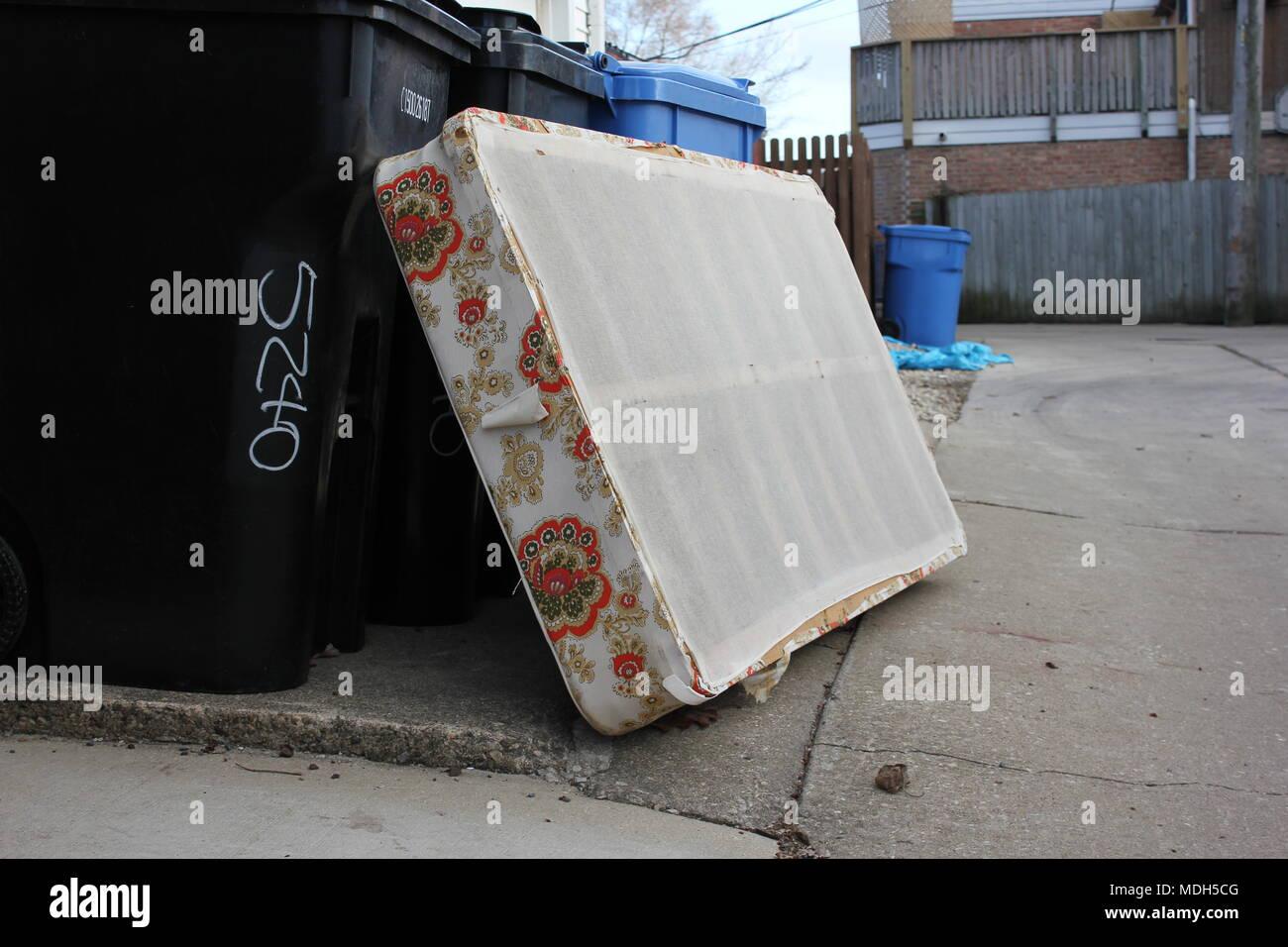 Utilizzate la casella materasso appoggiato contro la garbage lattine pronti per il ritiro di rifiuti al giorno. Immagini Stock
