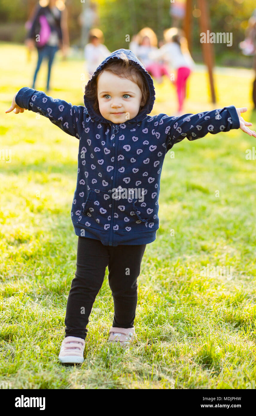Piccola bambina gioca felice nel parco all'aperto nella primavera in controluce. Immagini Stock