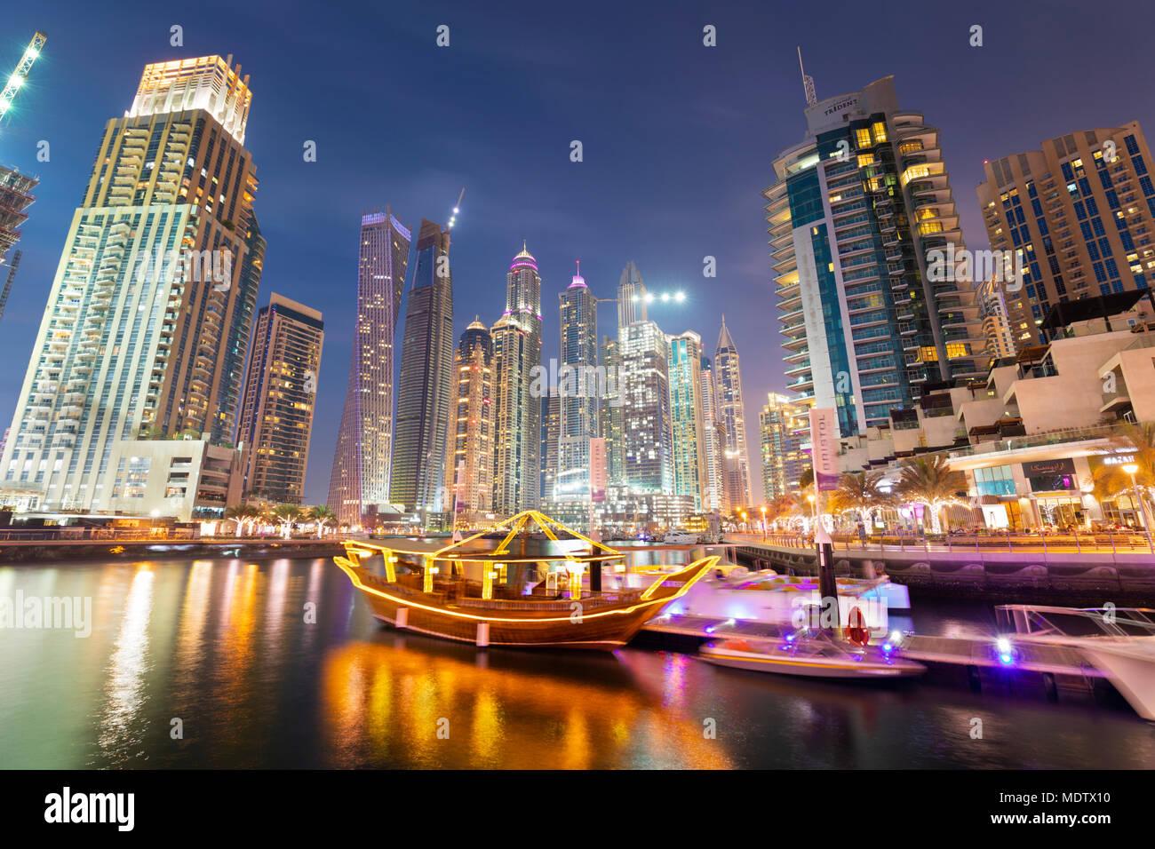 Architettura moderna con un giro turistico a bordo di un giunco sotto le torri illuminata di notte in Dubai Marina, Dubai, Emirati Arabi Uniti, Medio Oriente Immagini Stock
