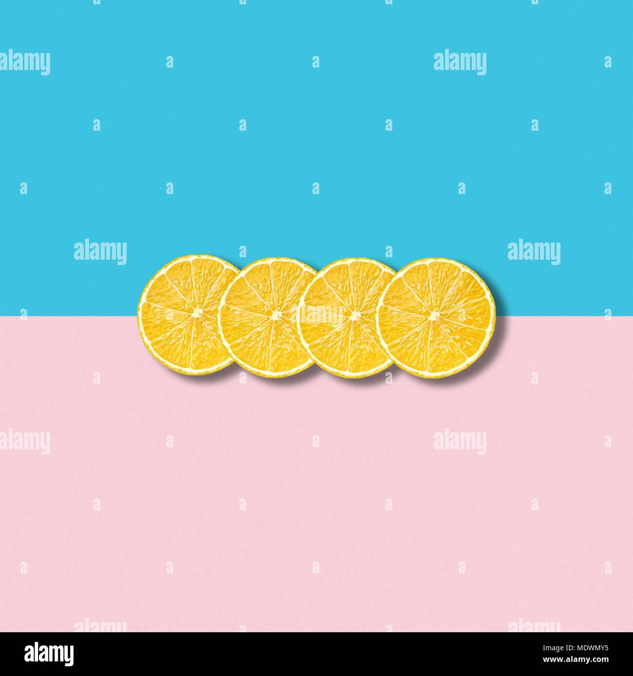 La minima illustrazione astratta con gruppo di fette di limone su rosa pastello e sfondo turchese Immagini Stock