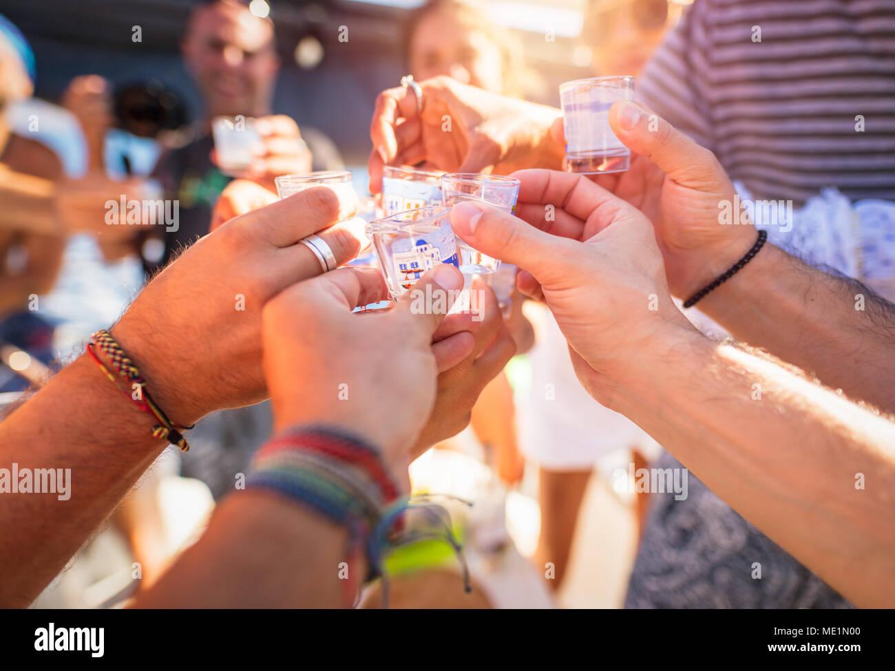 Primo piano di un uomo le mani con un bicchiere pieno di bevanda alcolica, parlando toast, saluti celebrando holiday, open air party, felice vacanza estiva Foto Stock
