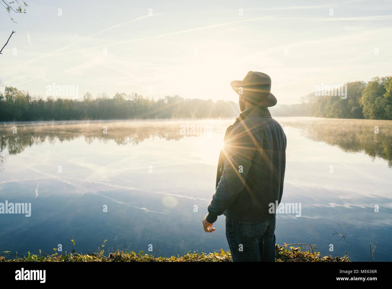 Giovane uomo di contemplare la natura in riva al lago di sunrise, primavera, in Francia, in Europa. Persone Viaggi relax nella natura del concetto. Immagine dai toni Foto Stock