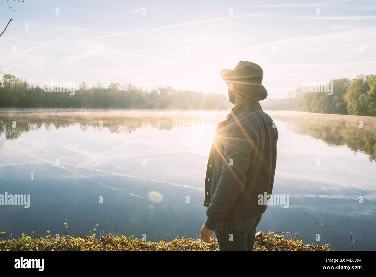 Giovane uomo di contemplare la natura in riva al lago di sunrise, primavera, in Francia, in Europa. Persone Viaggi relax nella natura del concetto. Immagine dai toni Immagini Stock
