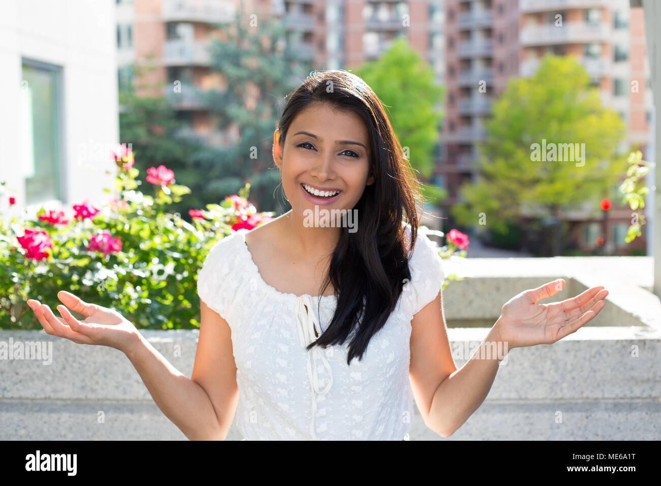 Closeup ritratto, felice giovane donna graziosa guardando scioccato sorpreso per l'incredulità, le mani in aria, a bocca aperta, gli edifici isolati, fiori sfondo. P Immagini Stock