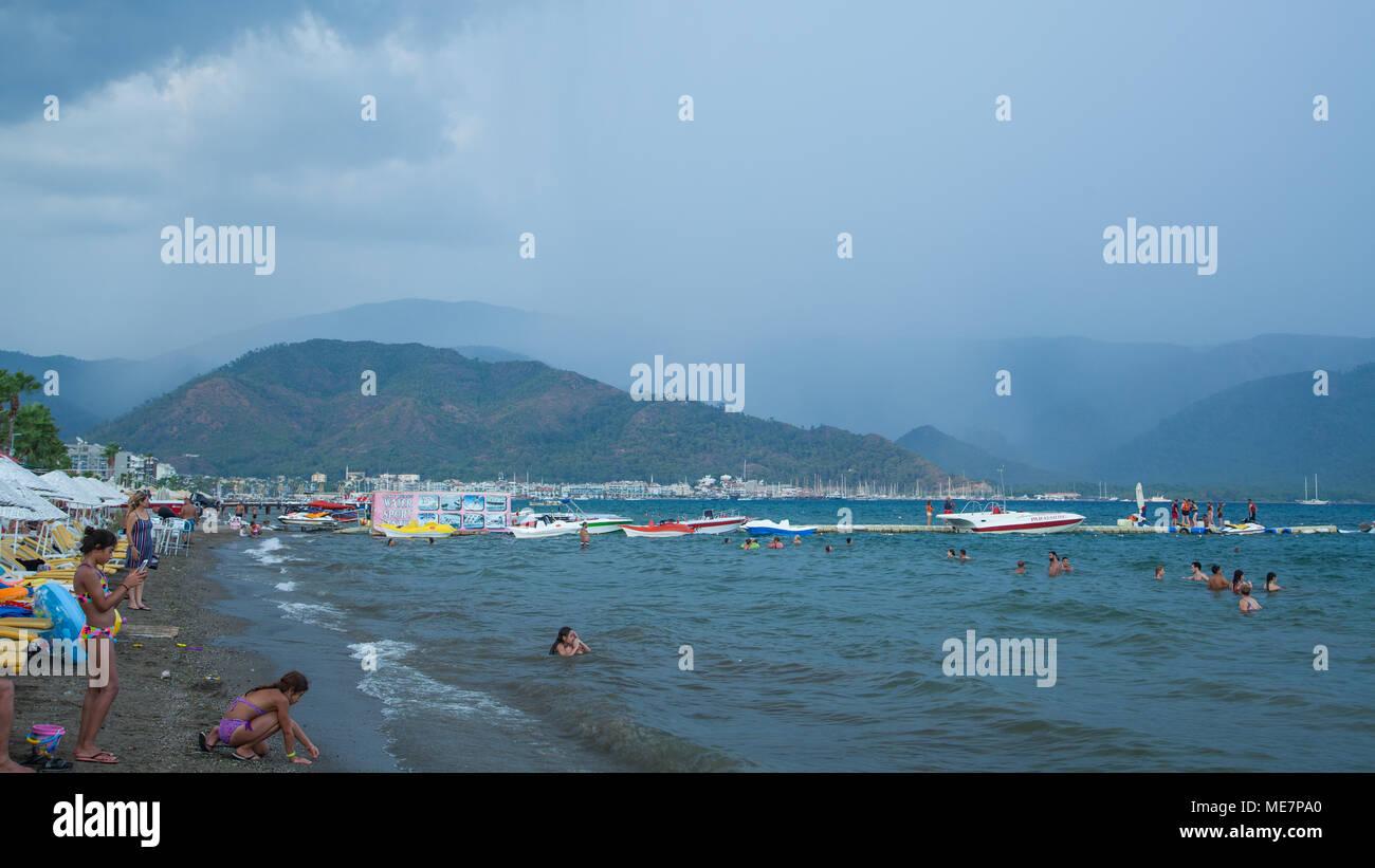 Persone bagnarsi nel mare contro uno sfondo di pioggia in montagna, Marmaris, Turchia Immagini Stock