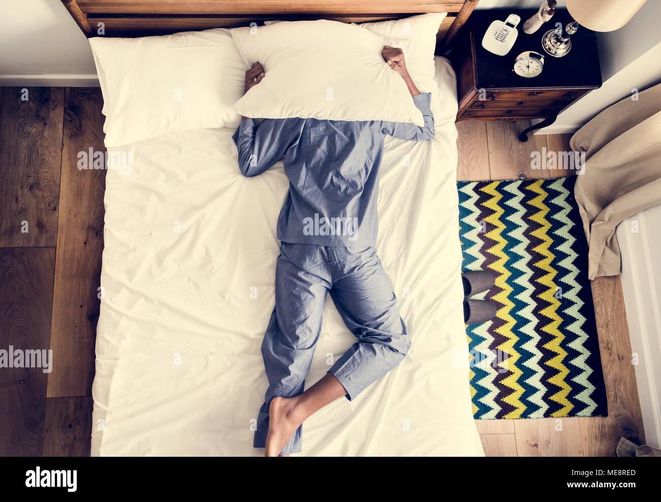 L'uomo sul letto insonnia e inquinamento acustico concept Immagini Stock