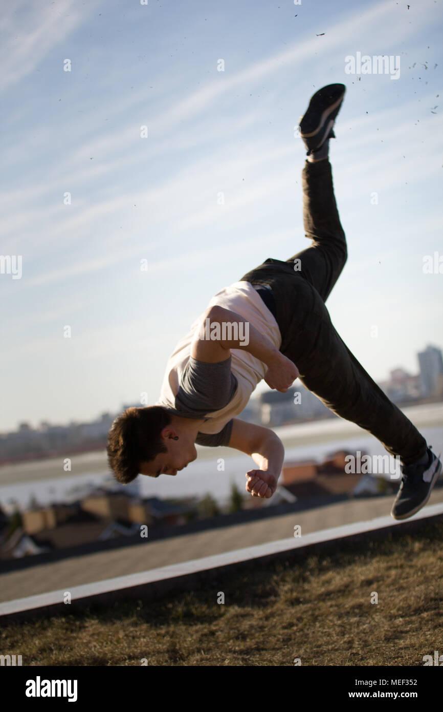 Giovane maschio sportivo acrobatico esegue trucchi salti nella parte anteriore della skyline Immagini Stock