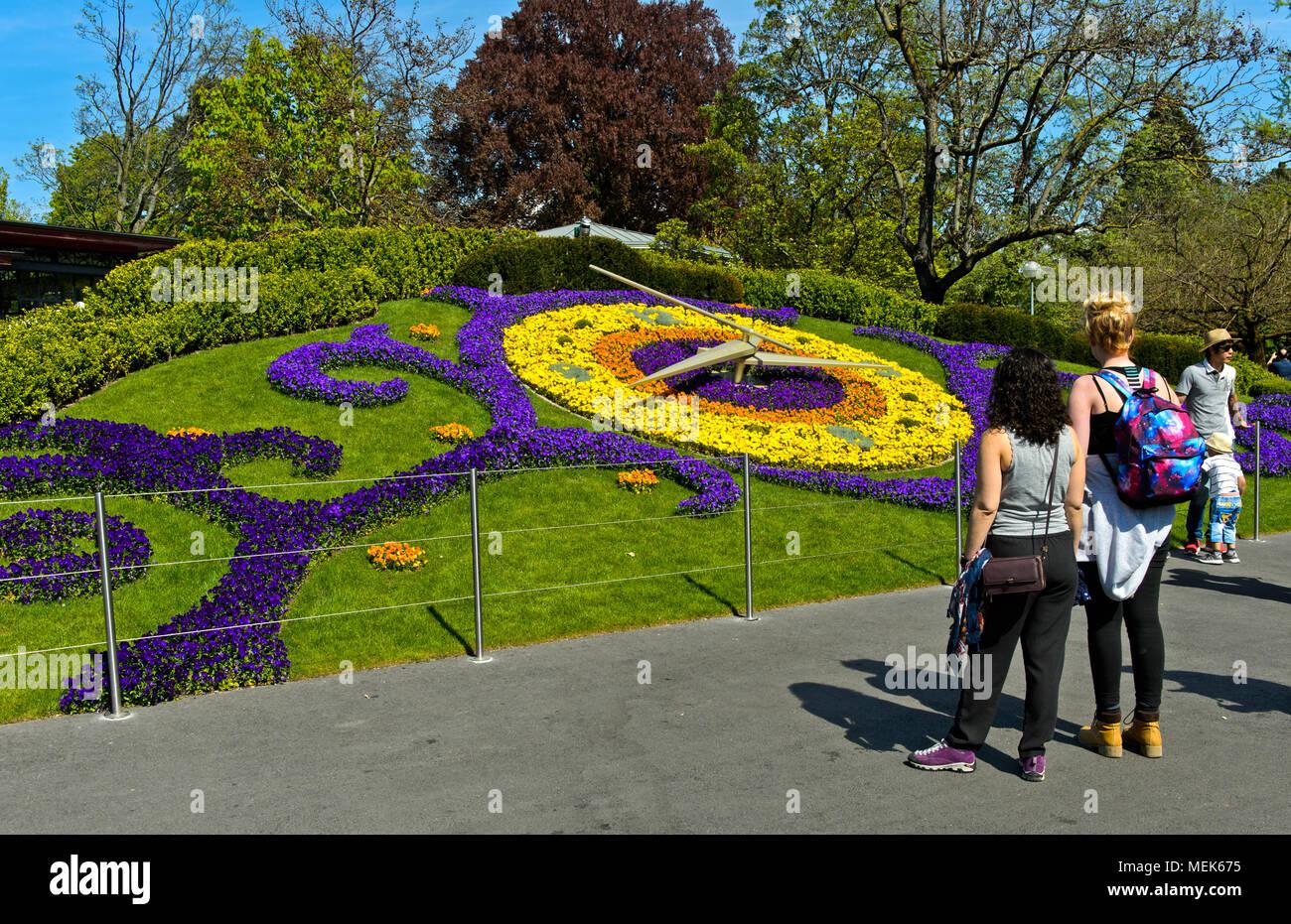 I turisti per quanto riguarda l'Orologio dei fiori, l'Horloge Fleurie, al parco Jardin Anglais, Ginevra, Svizzera Immagini Stock