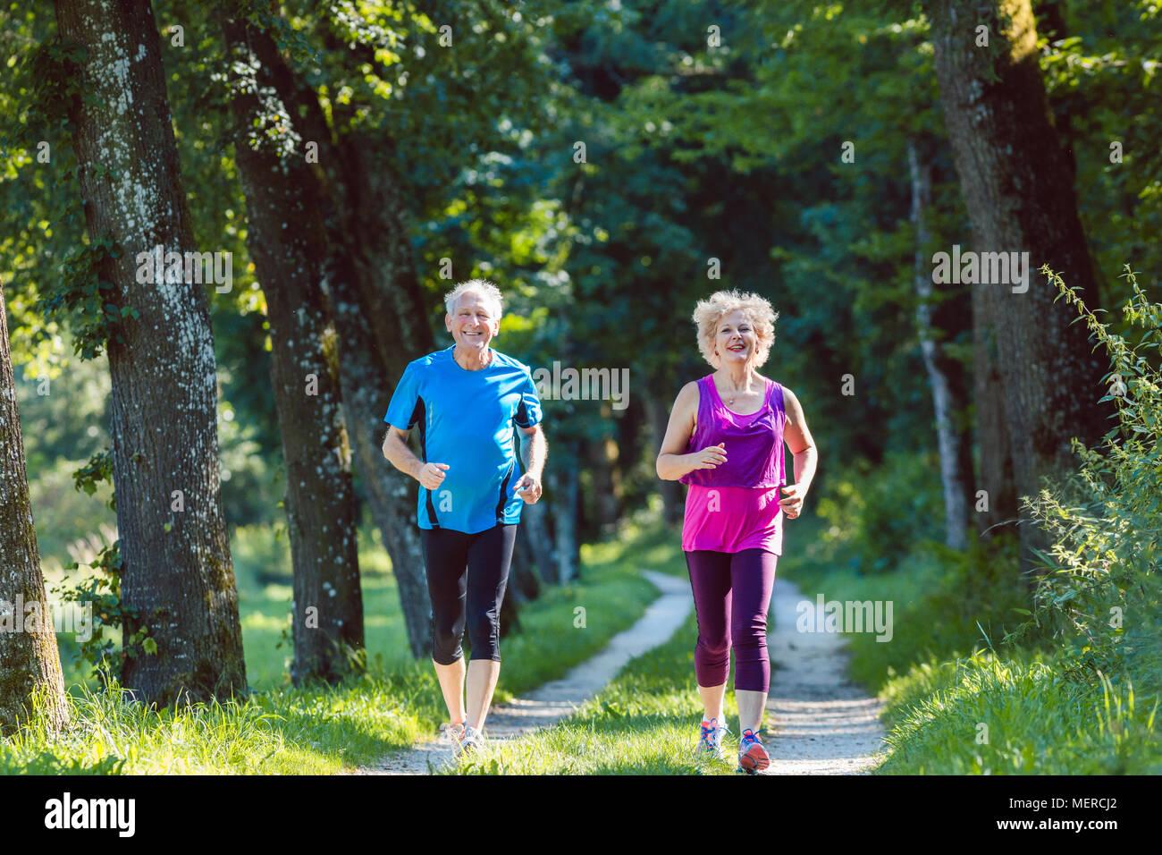 Due anziani attivi con uno stile di vita salutare sorridendo durante il jogging Immagini Stock