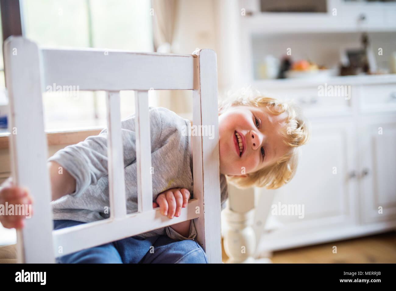 Un bimbo piccolo ragazzo seduto sulla sedia a casa. Immagini Stock
