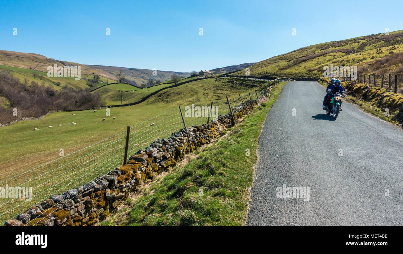Motociclisti godendo di strade vuote e le splendide viste in Swaledale su una bella giornata di sole, B6270, Yorkshire Dales Immagini Stock