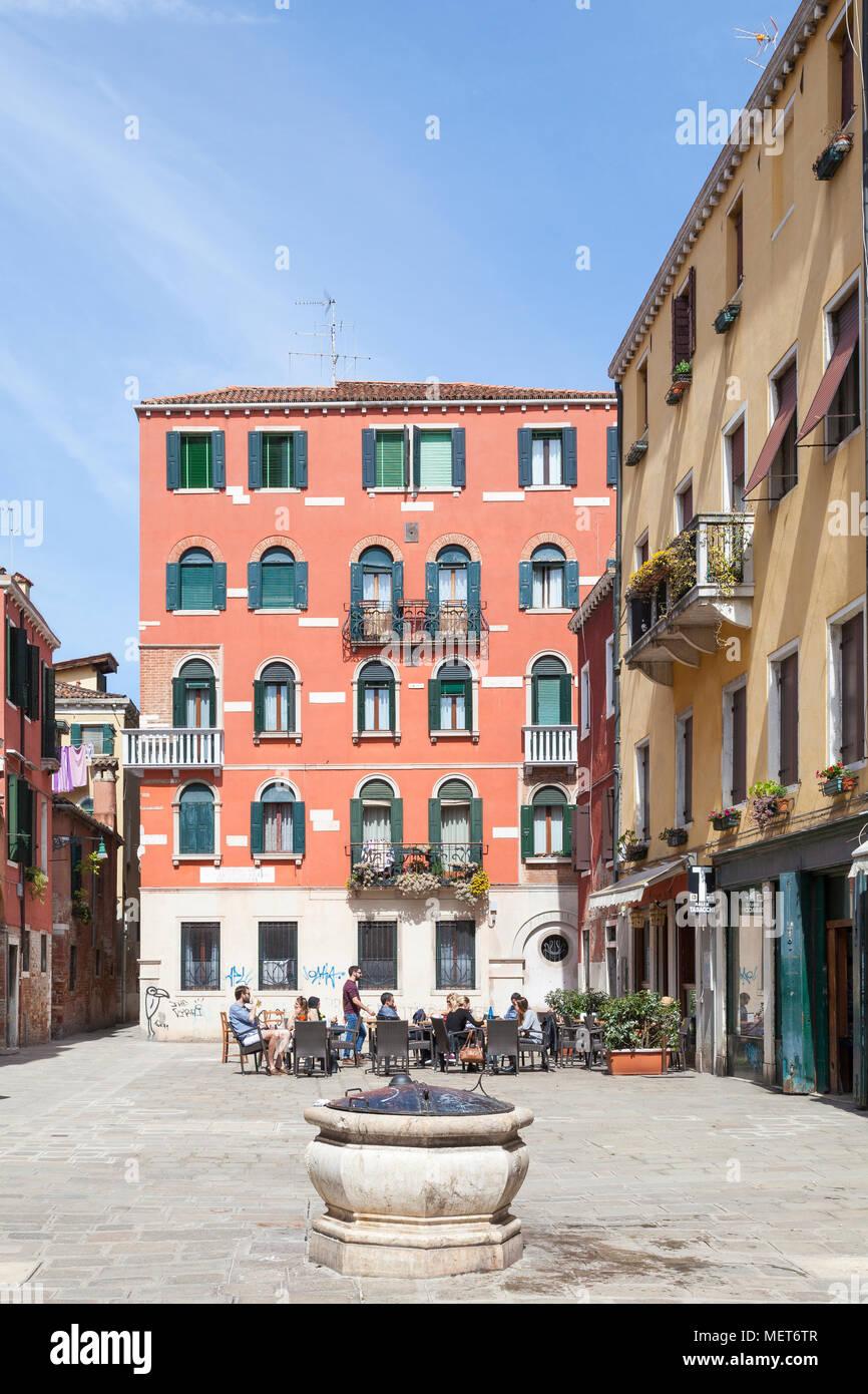I turisti rilassante al di fuori di un ristorante, Campo de Santa Giustina detto de Barbara, Castello, Venezia, Italia con un antico pozzo (testa pozzo) Immagini Stock
