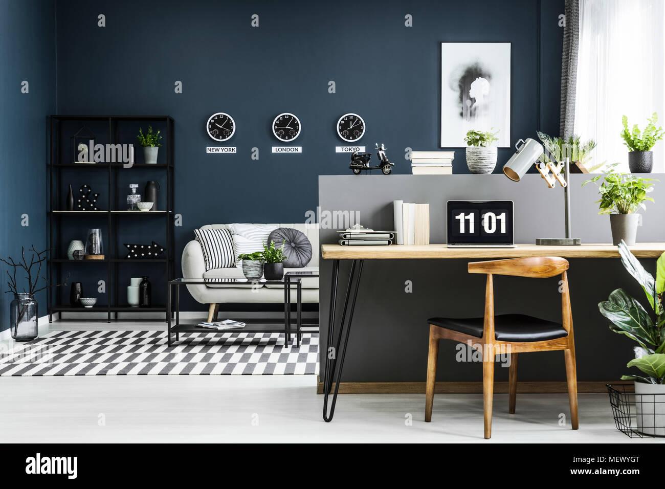 Spazio aperto home office interno con scrivania, sedia, piante e moderna area salotto in background Immagini Stock