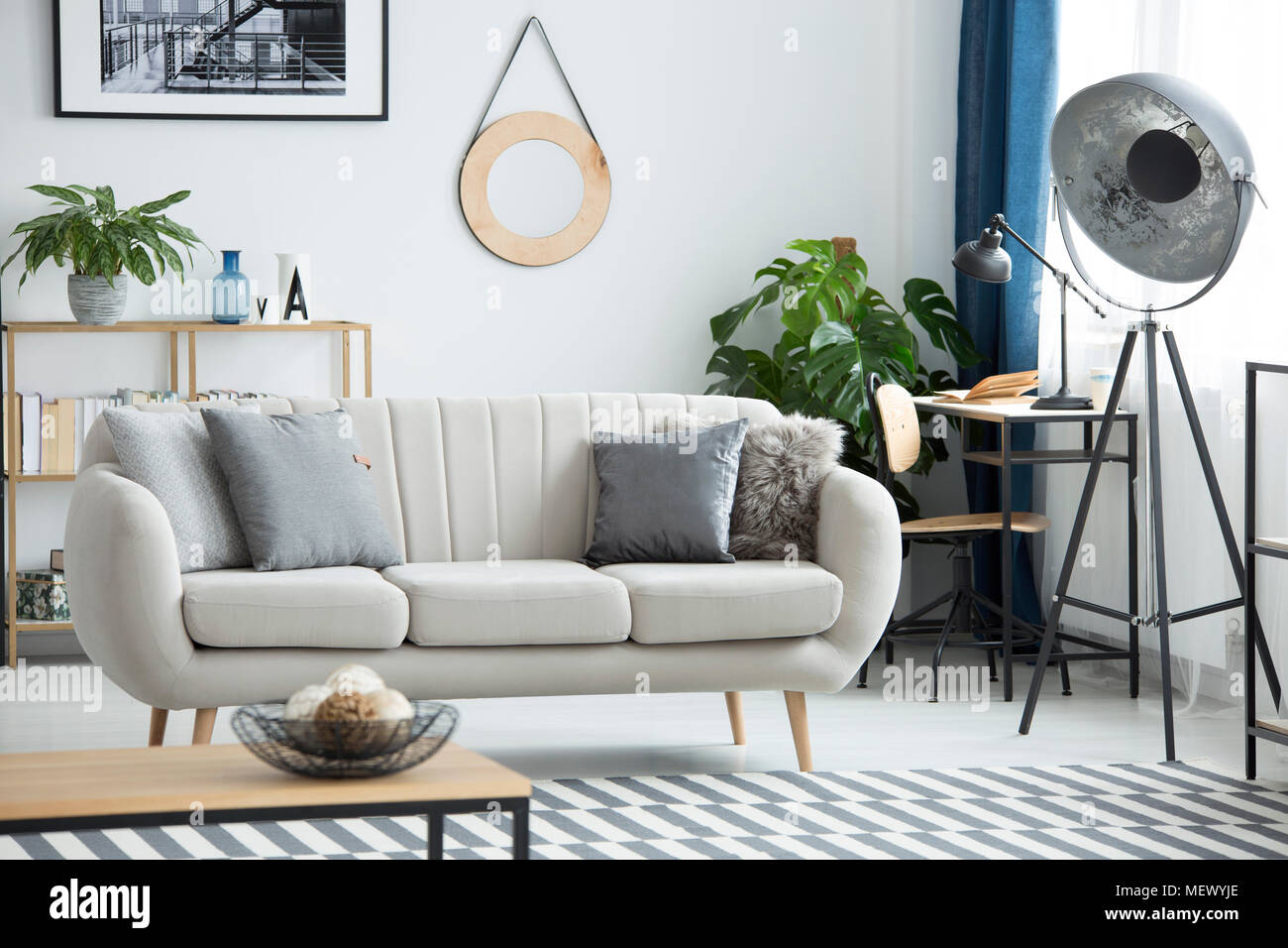 Lampada industriale accanto al divano in soggiorno interno con specchio rotondo sul muro bianco - Soggiorno con divano ...