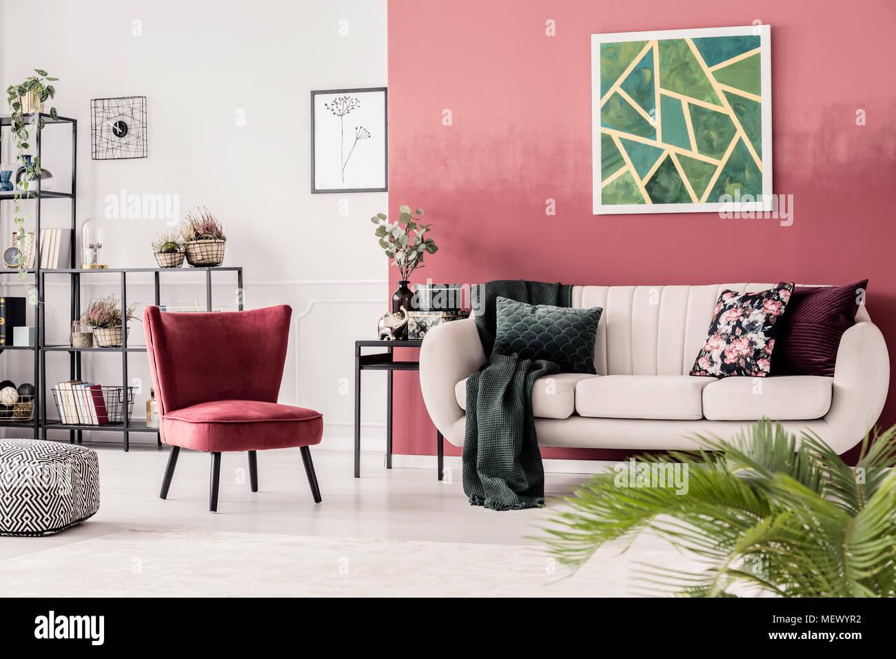 Poltrona rossa accanto al divano beige contro la parete verde con ...