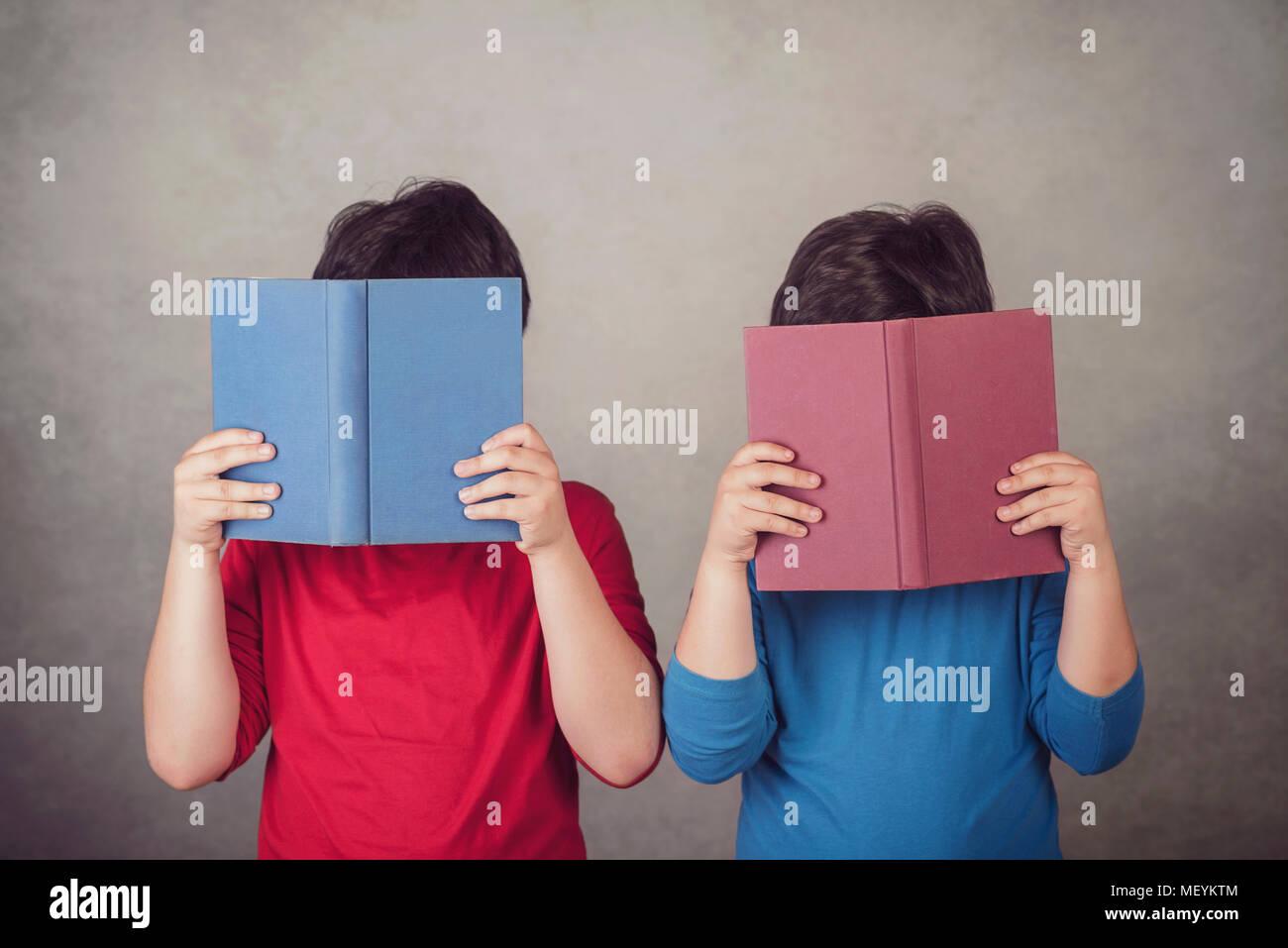 I bambini la lettura di un libro su sfondo grigio Immagini Stock