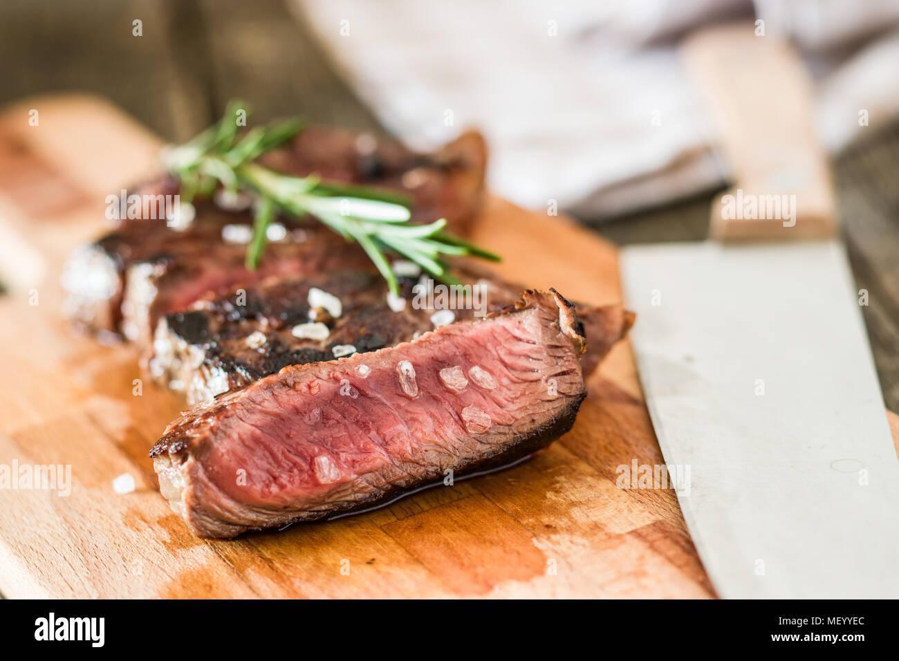 Fette di mezzo raro bistecca alla griglia sul bordo di taglio. Immagini Stock
