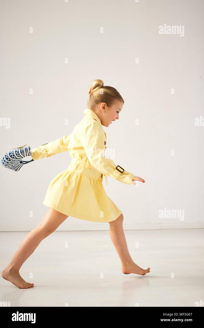 Ridere bambina correre a piedi nudi di fronte a uno sfondo chiaro Immagini Stock