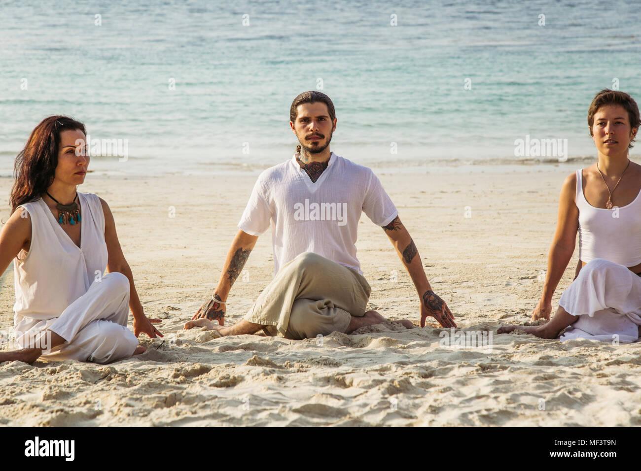 Thailandia Koh Phangan, tre persone fare yoga su una spiaggia Immagini Stock
