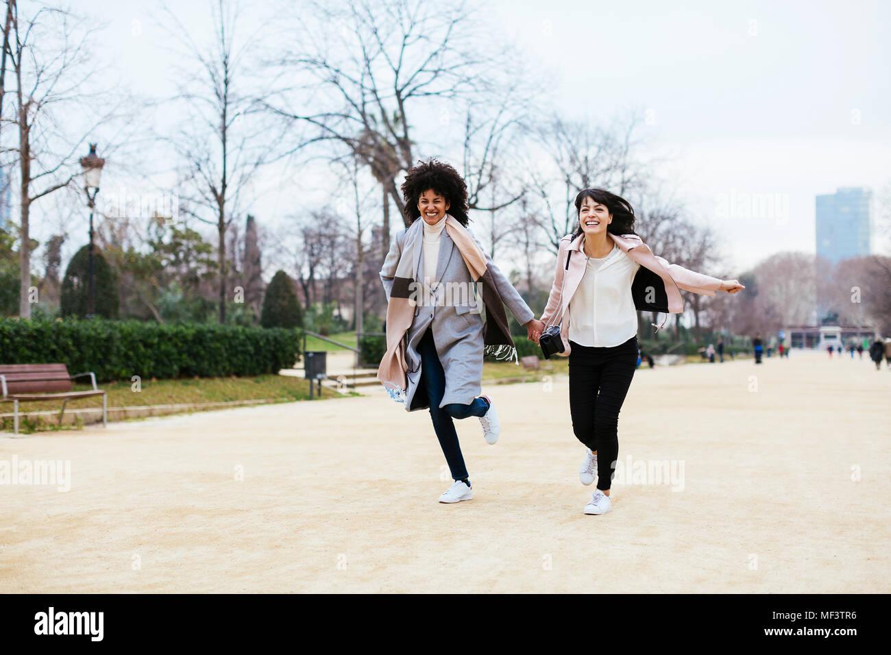 Spagna, Barcellona, due esuberante donne in esecuzione nel parco della città Immagini Stock
