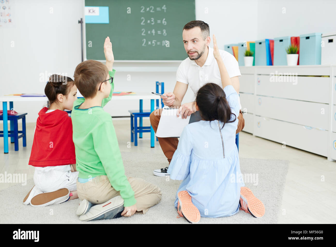 Studenti della scuola primaria alzando le mani e rispondere alle domande mentre è seduto sul pavimento e avente attività di matematica con insegnante maschio Immagini Stock