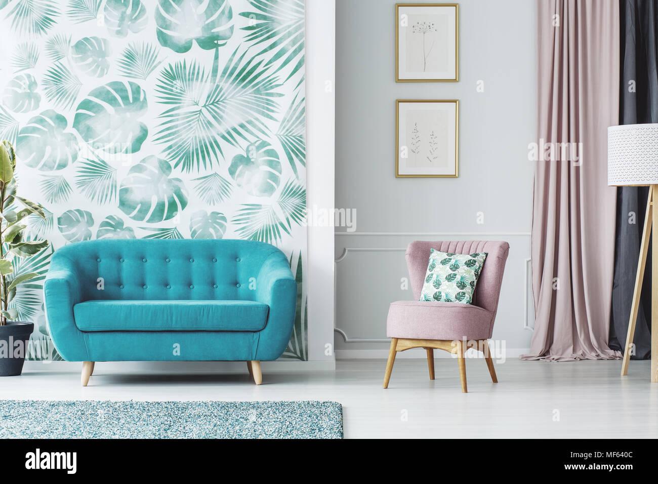Poltrona rosa accanto al divano blu in salotto interno con poster e carta da parati verde Immagini Stock