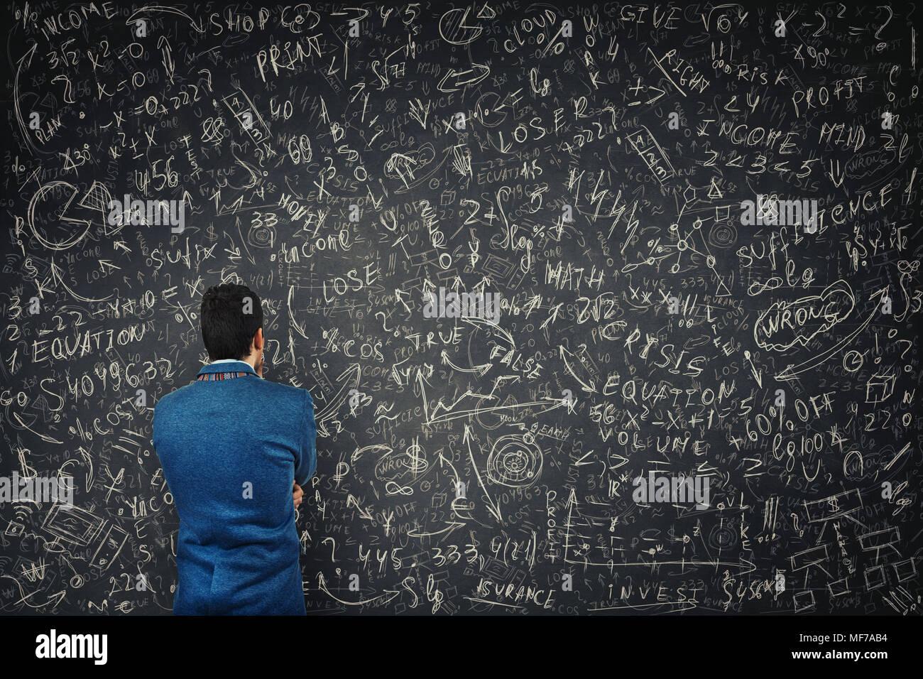 Vista posteriore di un imprenditore perplesso di fronte a un enorme blackboard tentare di risolvere hard matematica di calcolo, formula ed equazioni. Il pensiero di progetto Immagini Stock