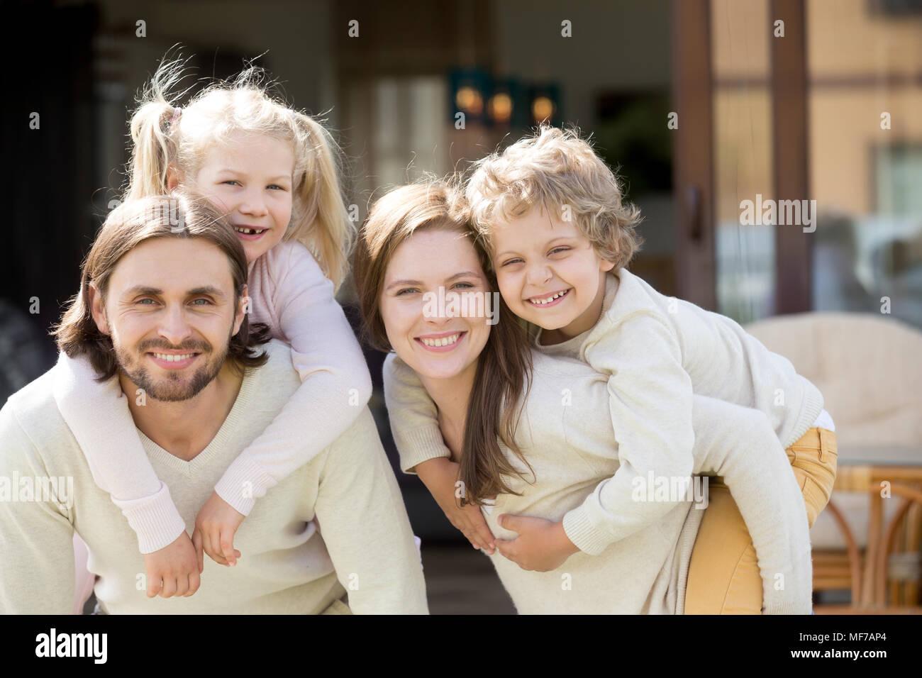 Genitori felici piggybacking bambini sul terrazzo della casa guardando è venuto Immagini Stock