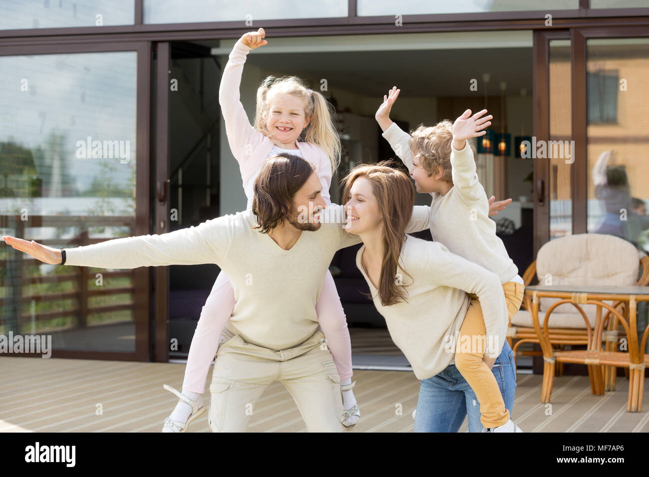 Sorridente genitori piggybacking giocando con i bambini a trascorrere del tempo Immagini Stock