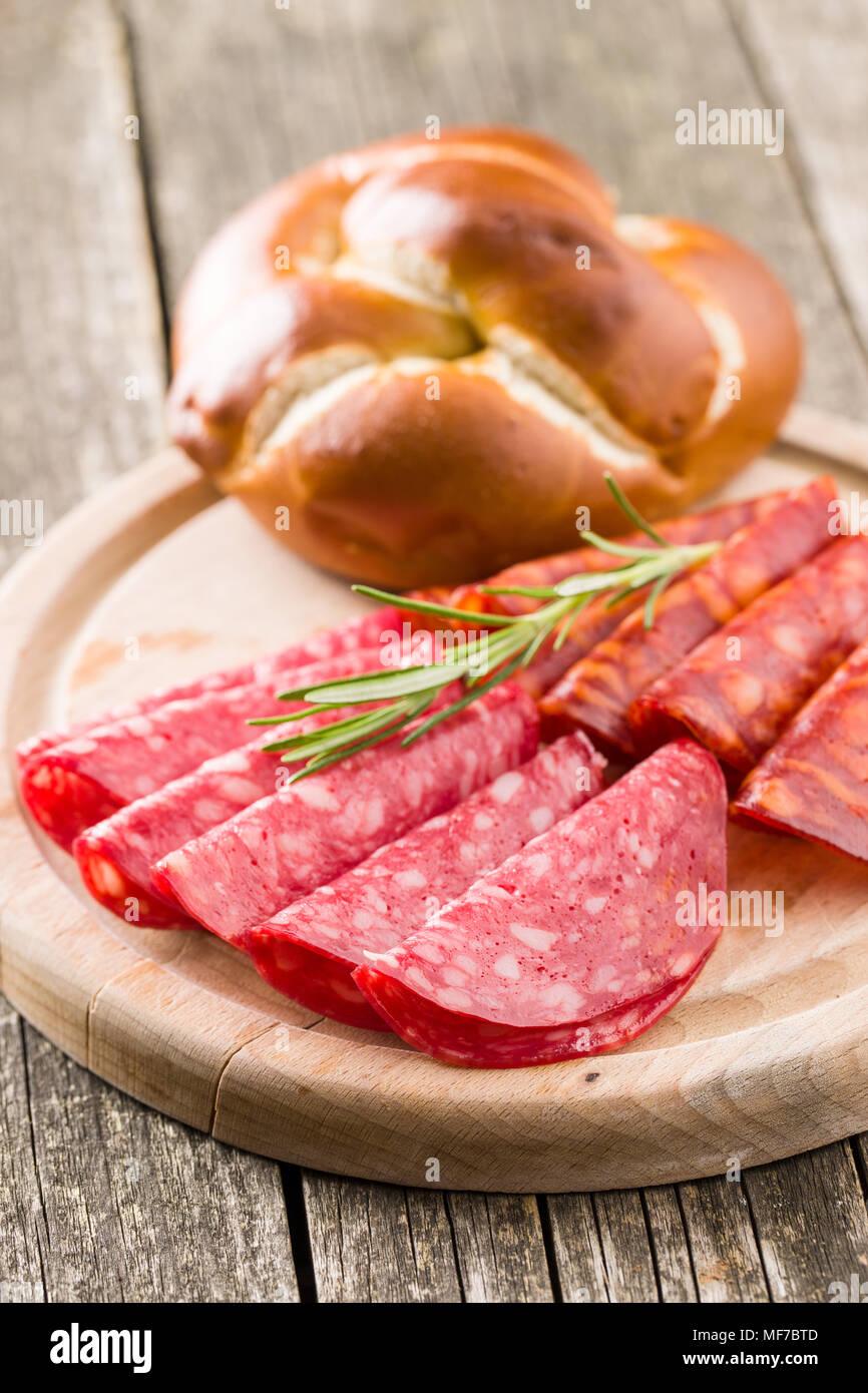 Fette di salame affumicato insaccato su tagliere. Immagini Stock