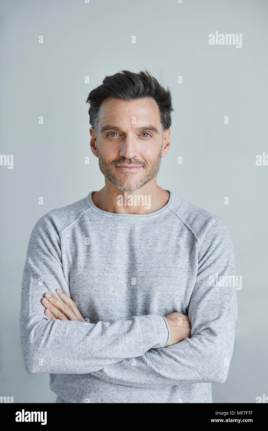 Ritratto di uomo sorridente con la stoppia indossando felpa grigio Immagini Stock