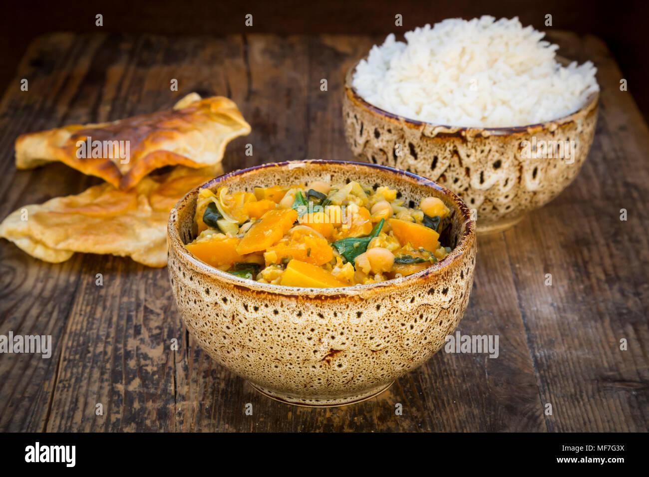 Piatto di curry con cavolfiore, butternut zucca, spinaci e coriandolo, papadam e riso Immagini Stock