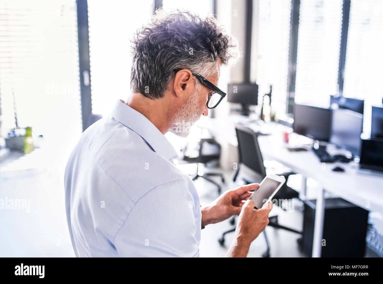 Imprenditore maturo in ufficio utilizza lo smartphone Immagini Stock