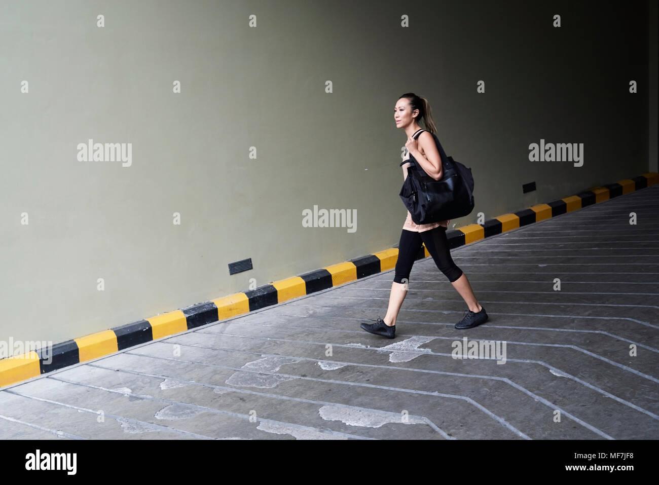 Fiducioso montare la donna a piedi a garage Immagini Stock