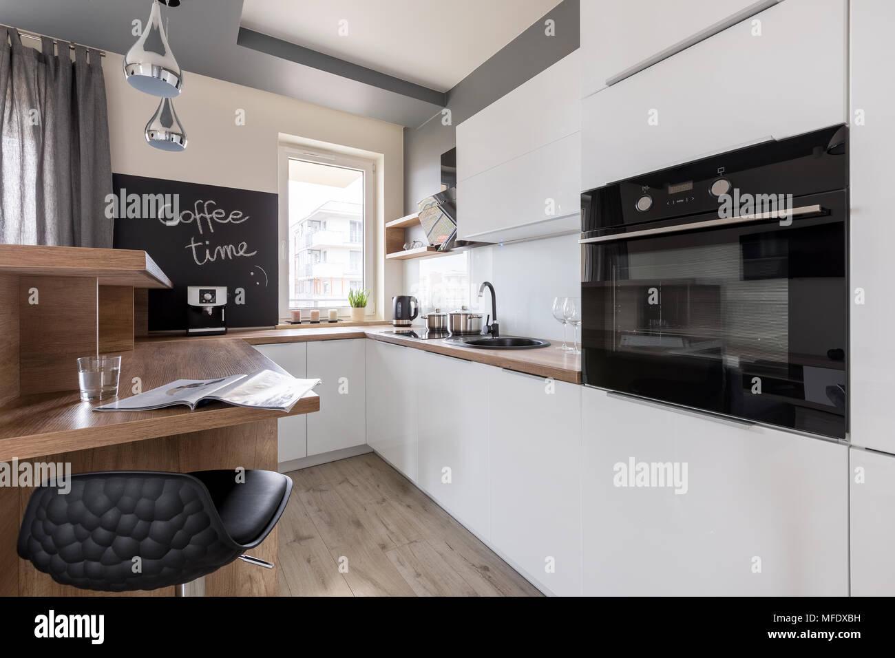 Cucina in stile contemporaneo con mobili bianchi e neri sgabello