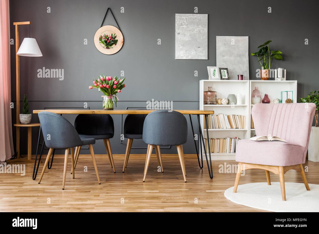 Poltrona Rosa Accanto A Sedie Grigio Al Tavolo Di Legno Con I Tulipani In Elegante Sala Da Pranzo Interno Foto Stock Alamy