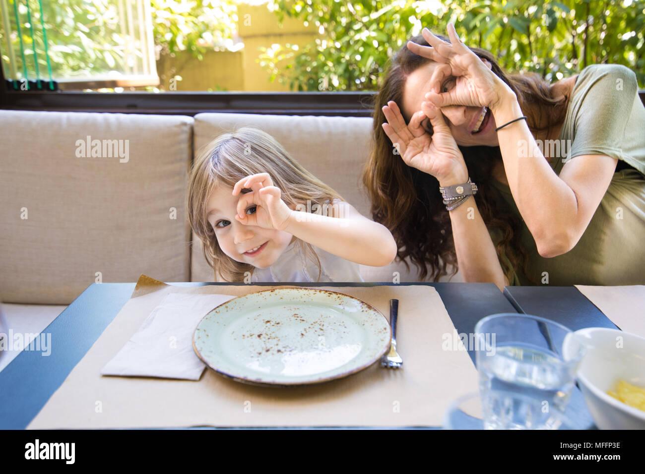 Famiglia divertenti espressione e gesto. Quattro anni di età felice bionda Ragazza donna madre teasing e smorfie con le dita negli occhi seduti nel ristorante Immagini Stock