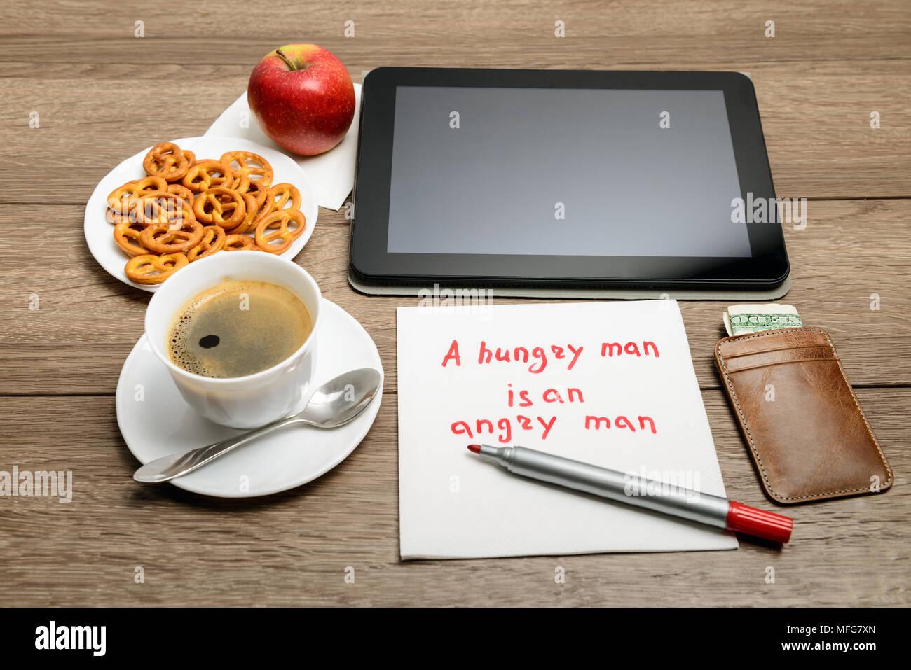 Tovagliolo scrittura proverbio del messaggio sul tavolo di legno con caffè, alcuni alimenti e tablet PC un uomo affamato è un uomo arrabbiato Immagini Stock