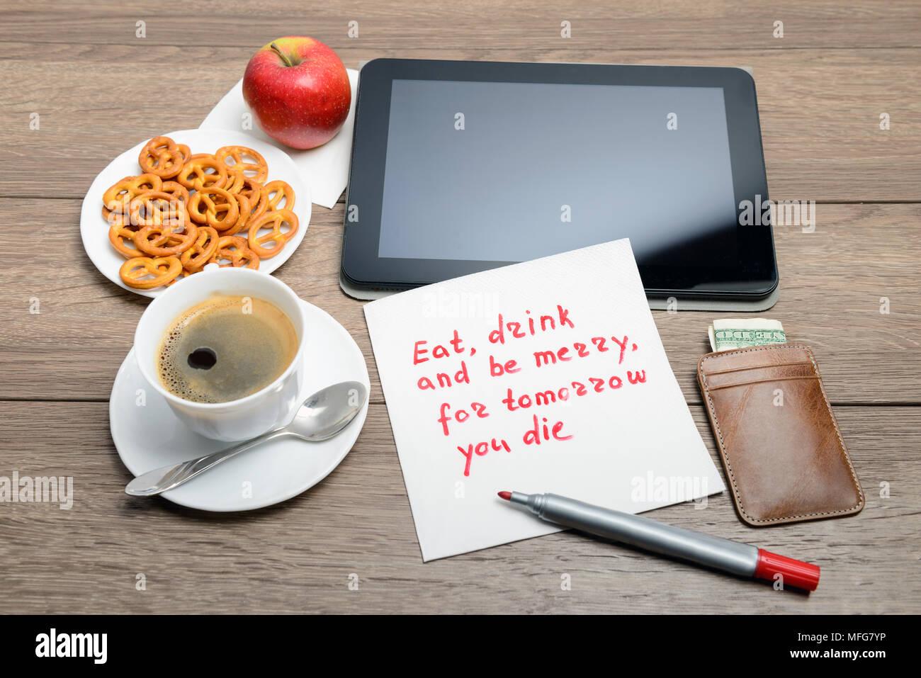 Tovagliolo scrittura proverbio del messaggio sul tavolo di legno con caffè, alcuni alimenti e tablet PC mangiare, bere e stare allegro, per domani si muore Immagini Stock