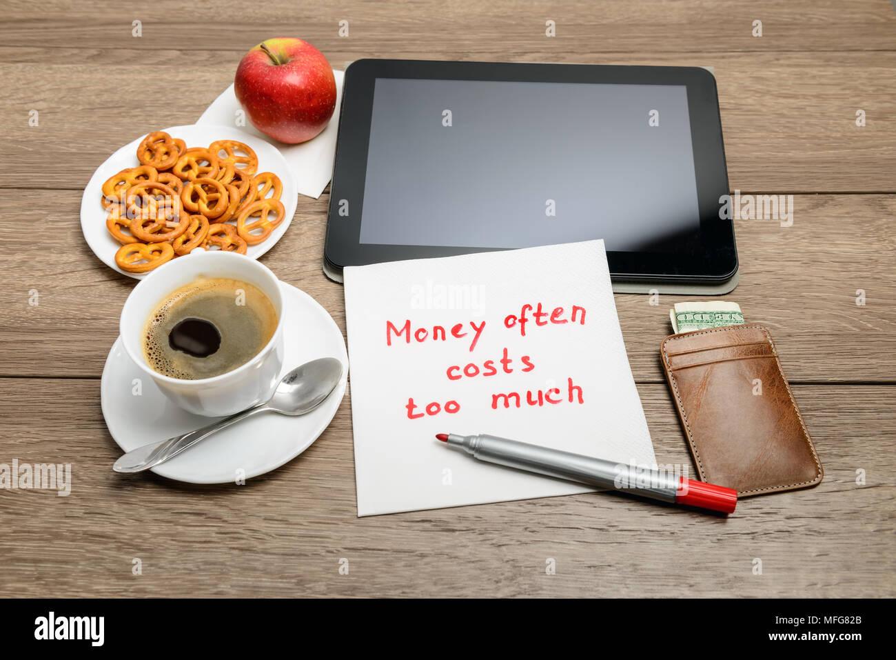 Tovagliolo scrittura proverbio del messaggio sul tavolo di legno con caffè, alcuni alimenti e tablet PC denaro spesso costa troppo Immagini Stock