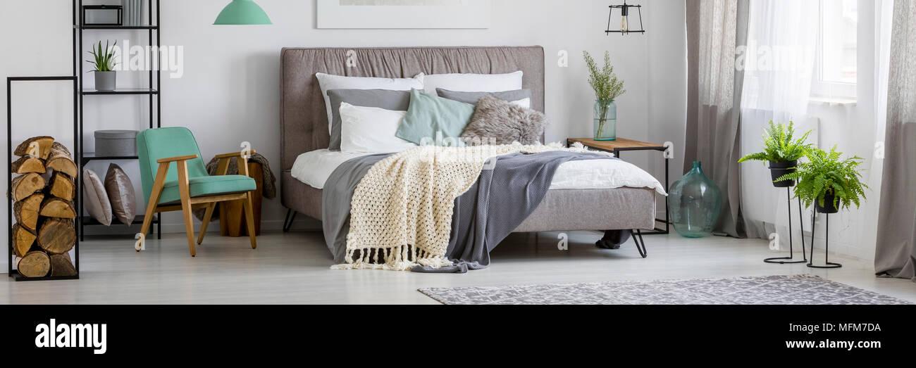 Accogliente, scandinavo interiore camera da letto con letto grande, piante, legno, poltrona, tappeto tende e lampada Immagini Stock