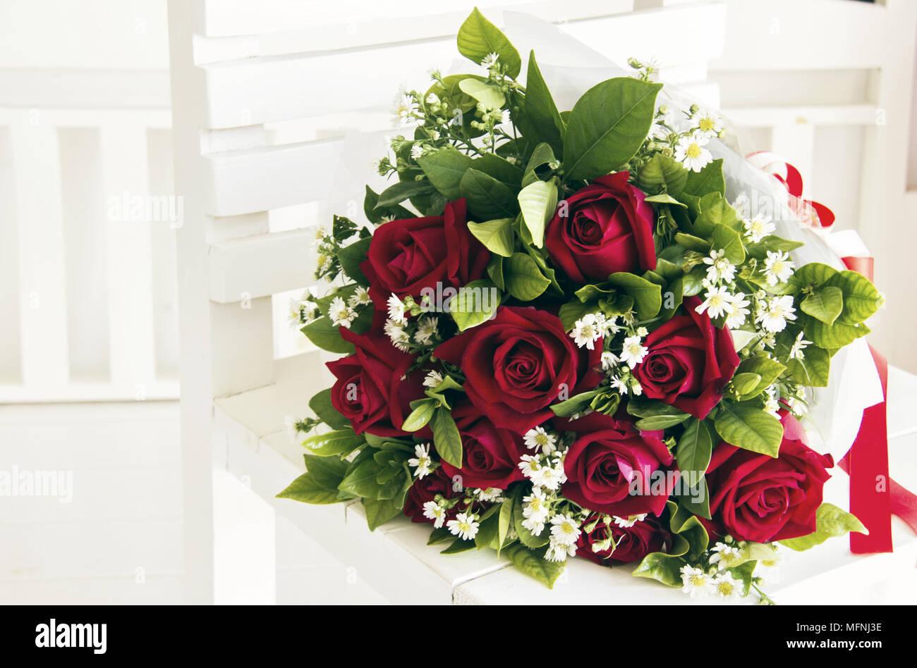 Un Mazzo Di Rose Rosse Sul Bianco Panca In Legno Immagine