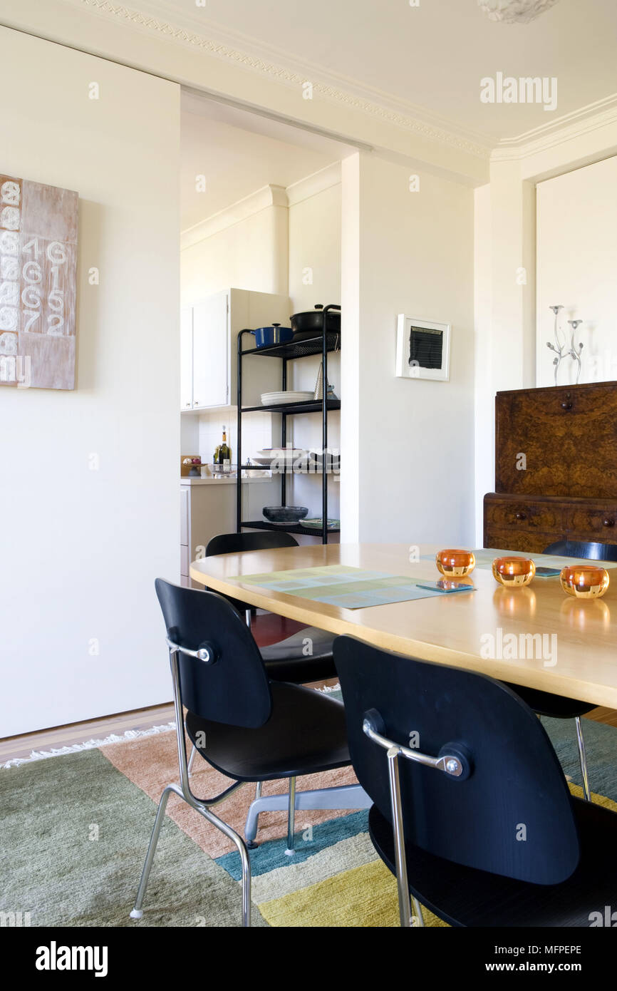 Sedie nere al tavolo di legno nella moderna sala da pranzo con porte ...