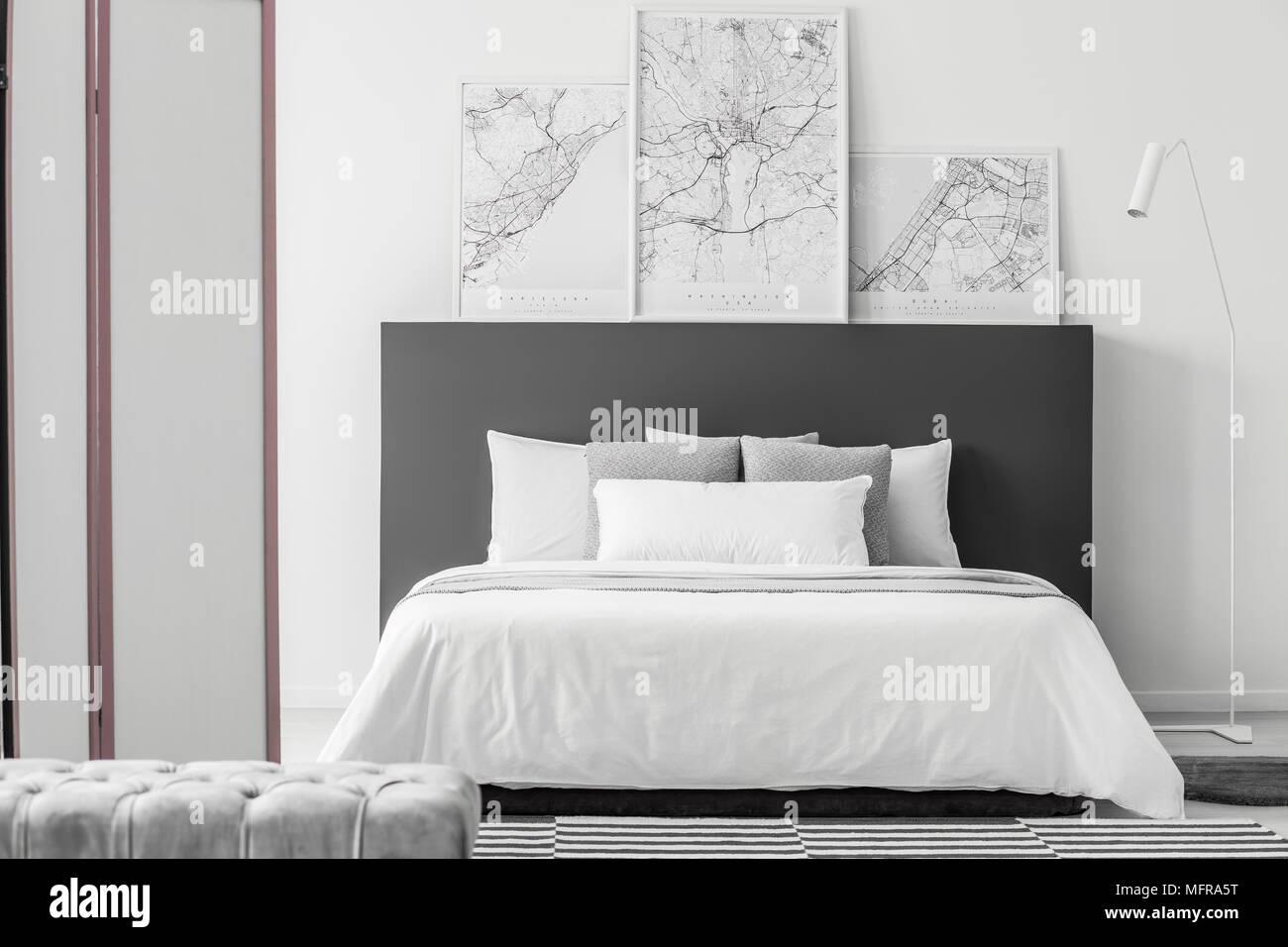 Grigio pouf in elegante camera da letto interno con mappe su nero ...