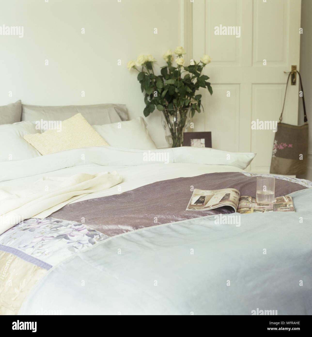 Camera da letto con letto matrimoniale con cuscini un vaso con rose ...